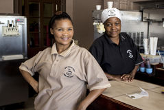 Portraits of two women at work. A waitress and a cook african ethnicity at their work looking at camera. Diaz Coffee Shop, Namibia Stock Images