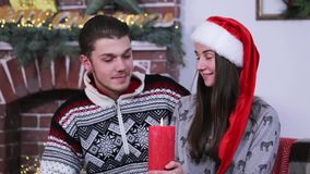 Portraits of young caucasian couple smiling and looking on a red burning candle. stock footage