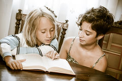 Portraits of young childs reading a book stock photos