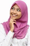 Portraits of young muslim woman smiling. While looking upstairs in white background Royalty Free Stock Images