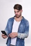 Portraitt του νεαρού άνδρα που χρησιμοποιεί το τηλέφωνό του Στοκ Εικόνα