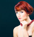 Portraiture of beautiful young female model woman. Girl with red hair made in studio on dark background Stock Photo