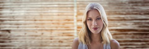 Portraiture of woman smiling against blurry wood panel Royalty Free Stock Images