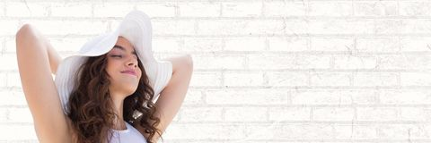 Portraiture of woman in summer hat relaxing against white brick wall. Digital composite of Portraiture of woman in summer hat relaxing against white brick wall Stock Image