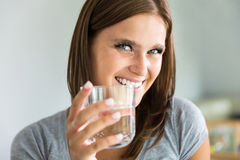 Portraiture of young woman with glass of water. Portraiture of young smiling woman with glass of water Royalty Free Stock Images