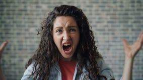 Portraot av den emotionella unga kvinnan som skriker skaka händer på tegelstenbakgrund lager videofilmer