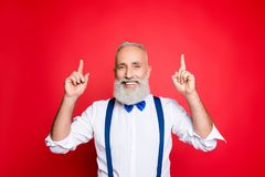 Portrat of confident, cheerful, joyful professional barber, stylist with blue bow and suspenders, in formal wear, pointing two royalty free stock images