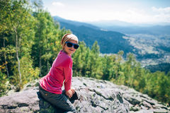 Portrat of happy little girl sitting on rocky cliff  in the moun Royalty Free Stock Image