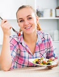 Portrate of young woman eating salad at kitchen. Portrait of happy young woman with chestnut hair eating salad at kitchen Royalty Free Stock Photos