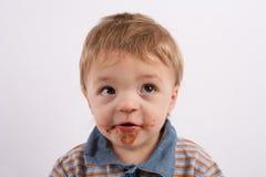 Portrati de um bebê engraçado com o seu chocolate sujo da cara Imagens de Stock