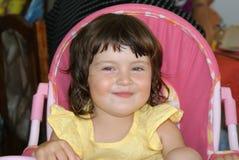 Portratit του ευτυχούς κοριτσιού στην καρέκλα παιδιών Στοκ Εικόνες