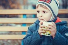 Portreit of a little boy drinking juice. Autumn portrait little boy thinks and drinking juice a tube royalty free stock photos