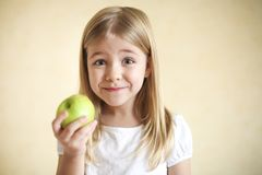 Little funny blonde girl with green apple. Portreit of little funny blonde girl with green apple Royalty Free Stock Photography