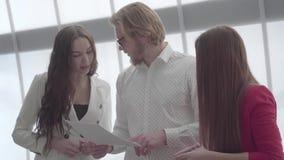 Portretów blondynów ufny mężczyzna wyjaśnia jego pomysł dwa żeńskiego kolegi stoi z obu stron on w a w szkłach zbiory