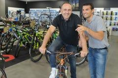 Portretów pozytywni mężczyzna zatrudnia roweru ot do wynajęcia sklep Zdjęcie Stock