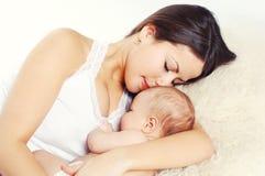 Portretów szczęśliwi potomstwa matkują dosypianie z dzieckiem na łóżku w domu, t Obrazy Stock