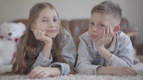 Portretów uroczy bliźniacy kłama na dywanie i zanudzający i wtedy w tym samym czasie patrzeją each inny zbiory