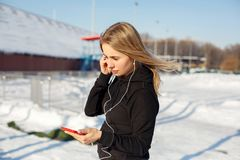 Portret śliczna blondynki dziewczyna słucha muzyka podczas gdy chodzący w dół ulicznego mienia czerwony telefon w ręce Śnieg kłam fotografia royalty free