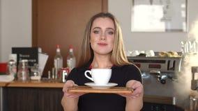 Portret śliczna młoda barista dziewczyna, uśmiecha się kawę i oferuje ci zdjęcie wideo