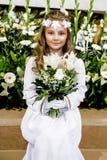 Portret śliczna mała dziewczynka na bielu wianku na pierwszy świętego communion tła kościelnej bramie i sukni obraz royalty free