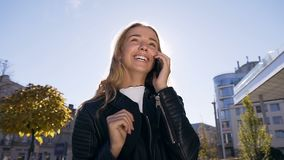 Portret ładna blondynki dziewczyna opowiada na smartphone i ono uśmiecha się podczas gdy chodzący na ulicie i cieszący się miasto zbiory