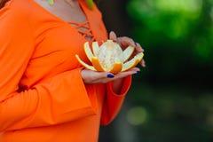 Portret ładna czerwona włosiana kobieta z soczystą wyśmienicie pomarańcze przy lato zieleni parkiem Obraz Stock