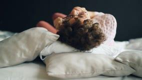 Portret ładna dama z ciemnym kędzierzawym włosy w szkłach i przypadkowej odzieży kołysaniem się w łóżku z uradowanym uśmiechem i  zdjęcie wideo