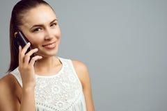 Portret ładna dziewczyna ono uśmiecha się i opowiada na telefonie komórkowym zdjęcia royalty free