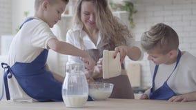 Portret ładna kobieta i jej dwa syna gotuje robić ciastu w kuchni chłopiec pomaga matki robić jedzeniu mama zbiory