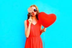 Portret ładna kobieta z lizaka cukierkiem, lotniczy balon na błękicie Zdjęcia Royalty Free