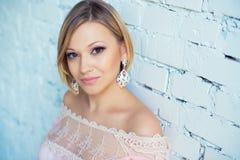 Portret ładna młoda blond kobieta z krótkim włosy na tle biały ściana z cegieł Zdjęcia Stock