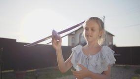 Portret ładna mała dziewczynka bawić się z małym zabawka samolotem w górę Dziecko wydaje czas outdoors w podwórko zdjęcie wideo