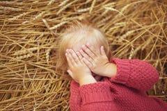 Portret ładna mała dziewczynka kłama na ucho banatka i zamyka jego oczy Obraz Stock