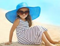 Portret ładna mała dziewczynka relaksuje odpoczywać na plażowym pobliskim morzu w pasiastej sukni słomianym kapeluszu i Zdjęcia Royalty Free