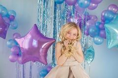 Portret Ładna mała dziewczynka siedzi z mnóstwo kolorów balonami i trzyma włosy Obrazy Royalty Free