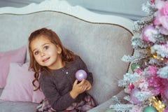 Portret Ładna mała dziewczynka trzyma Bożenarodzeniowy zabawkarski gotowego na kanapie blisko choinki Fotografia Royalty Free