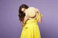Portret ładna zmieszana młoda kobieta w kolor żółty sukni nakrycia twarzy z lato kapeluszem na pastelowym fiołku obrazy royalty free