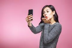 Portret ładny młodej kobiety dosłania powietrza buziak podczas gdy stojący selfie odizolowywającego nad różowym tłem i brać obrazy stock