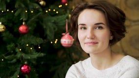 Portret ładny, ono uśmiecha się, brunetki dziewczyna świętuje nowego roku przed choinką Potomstwa, piękna kobieta zdjęcie wideo