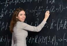 Portret ładny uczeń robi maths na blackboard Zdjęcia Stock
