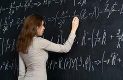 Portret ładny uczeń robi maths na blackboard Obrazy Royalty Free