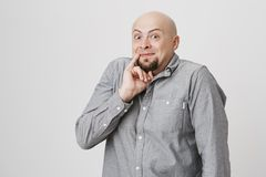 Portret łysy brodaty mężczyzna trzyma jego pinky pobliskiego usta nad białym tłem z śmiesznym wyrażeniem Facet jest pewny up to zdjęcia stock