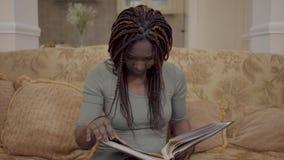 Portret śliczna amerykanin afrykańskiego pochodzenia kobieta ogląda fotografie w dużym leatherback photobook z ona z dreadlocks zbiory