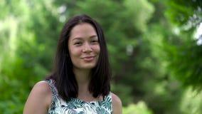 Portret śliczna azjatykcia kobieta gapi się z oczami Zielony park na tle zbiory wideo