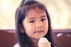 Portret śliczna azjatykcia mała dziewczynka je lody rożek Fotografia Royalty Free