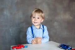 Portret śliczna chłopiec bawić się z samochodami, niezależne dziecko gry Preschool chłopiec bawić się z zabawkarskimi samochodami obrazy royalty free
