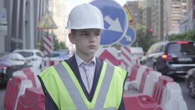 Portret śliczna chłopiec jest ubranym garnituru, zbawczego wyposażenia i konstruktora hełma pozycję na ruchliwie drodze w a zdjęcie wideo