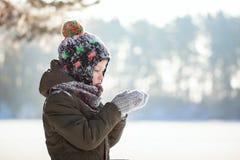 Portret śliczna chłopiec w ciepłym odzieżowym dmuchaniu na śniegu outdoors podczas opad śniegu w zima słonecznym dniu zdjęcia royalty free