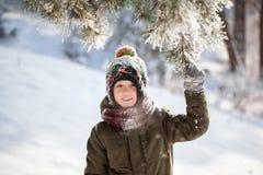 Portret śliczna chłopiec w ciepłym odziewa bawić się outdoors podczas opad śniegu w zima słonecznym dniu zdjęcia royalty free