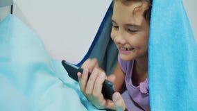 Portret śliczna dziewczyna pod koc z smartphone  zbiory